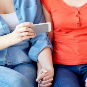 close up of lesbian couple with smartphone at home